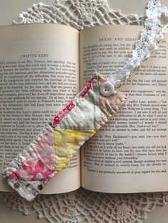 """This is a pretty way to mark the page in your latest read! These cute bookmarks have been handmade with love and are made from a vintage quilt piece. They are hand sewn around the edge and embellished with a decorative button and lace and/or ribbon at the top to help keep your place. Bookmarks measures approximately 1 ¾"""" wide X 6"""" long. They make great gifts for teachers, family, co-workers, bridesmaids, thank-you gifts, birthdays, valentines, Mothers Day, or stocking stuffers. **I lo..."""