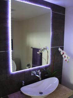 Contemporary powder room with a stylish mirror lit with LEDs from behind