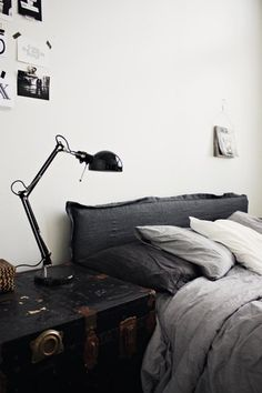Love the dark/many shades of grey against the bright white wall, and the textural trunk as a side table