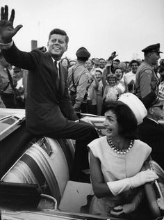 Senator John F. Kennedy and Jacqueline Kennedy ride in the back of a convertible in the motorcade from the Barnstable Municipal Airport after Senator Kennedy's return from the 1960 Democratic National Convention.