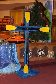 Transform a wooden cross from Easter services to use at VBS. This one was made using chicken wire and blue tablecloths. Wrap tablecloths around the chicken wire. Secure with tape. Take four oars and wire ties and attach them over the blue table cloths. To hold them all in place, wrap a few bungee cords around the middle of the wire ties. Budget friendly tip! Tablecloths were purchased at dollar shops.