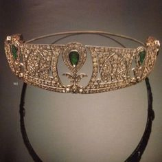 A Chaumet diamond and emerald belle epoque tiara, 1905. Designed as approx six panels with arthemion mofits, interspersed with spaces for upright, pear-shaped emeralds surrounded by diamonds.