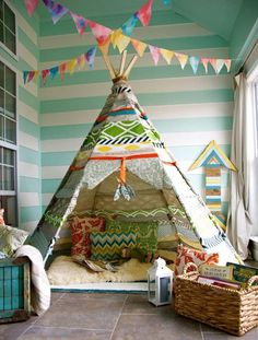 Oh goodness, I am in love with this sweet kids room/play area.  Mint green striped walls and colorful accessories.  Inviting tee-pee with pillows.  Perfect little reading nook.