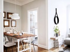 Open dining space with a reclaimed wood table, modern chairs and a modern pendant light