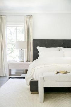 Cream French pleat curtains hang from a window positioned behind a light gray wood nightstand lit by a white pierced lamp.