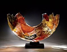 Memory by Caleb Nichols. A commanding form rendered in soft shades of cognac, green, and rose, this highly textured piece is created from blown glass forms that have been deliberately broken, then recombined and fused together into a stunning sculpture that glows in the light. Each piece is unique and will vary. Limited edition of 35.