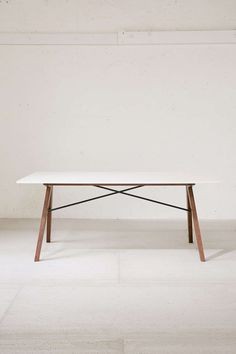 The Spirit Dining Table combines industrial cross-steel feature with splayed legs inspired by mid-century modern sensibility.