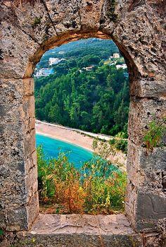"""Valtos beach, seen """"through"""" the walls of the Venetian castle of Parga town, Preveza, Epirus, Greece."""