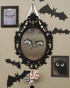 Indoor halloween decorations - mirror with glowing eyes. Looks like framed foil with painted-on eyes... Cute!
