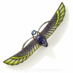 Silver Plique-a-Jour Egyptian Revival Winged Scarab Brooch. Boasting a 3 1/2 inch wingspan, a lapis lazuli scarab flies through the air, clasping a pair round faceted aquamarine colored stones, in this exotic Egyptian Revival brooch. Crafted in silver with translucent yellow and bluish-gray plique-a-jour enamel.