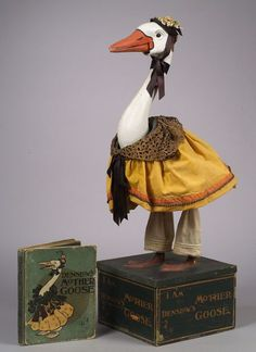 Rare Advertising Automaton of Denslow's Mother Goose, with painted papier-mache head articulated at the neck and beak, webbed papier-mache feet, standing on dark-green paper-covered wood base with printed gilt borders and lettering on four sides I am Denslow's Mother Goose.