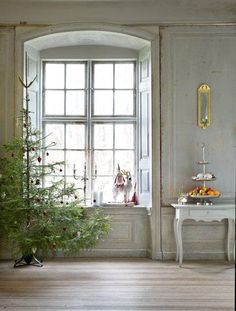 Beautiful architecture in Swedish room with arched window and Christmas tree. Elegant Christmas decoration. #Scandinavianstyle #holidayinspiration