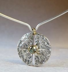 Heavily textured silver split disk with a light green spinel set in 14K yellow gold.  I've hung it from a silver neck wire.  Anna Vosburg Design