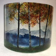Misty Blue Ridge Mountain Fall Overlook IV by Amanda Taylor. This fused and cast glass curved panel, with silhouettes of the Blue Ridge Mountains in the background and the fall colored trees in the foreground, has the feel of driving down the Blue Ridge Parkway in the fall and looking out at the distant hazy mountains. The semi-transparent quality of the glass is emphasized when placed in a lighted cabinet or in front of a window on a deep window sill. The glass panel was fired three times…