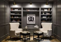 Gray paneled den features a focal wall lined with gray built-in shelves and cabinets illuminated ...