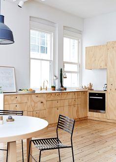 Love the raw wood cabinets with beautiful wood grain, raw wood floor, blue pendant light.