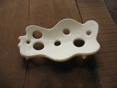 Small holes allow gentle breezes to waft about your soap, drying it so it doesnt get all gummy and nasty. it stands on wee ceramic feet.