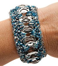 Using simple crochet stitches and beautiful metallic thread, you can recycle pull tabs from beverage cans into this fashionable and functional piece of wearable art -- for yourself or for a unique gift. here for larger image.