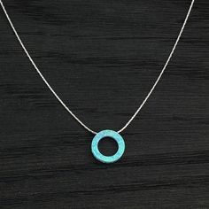 Shimmering blue fire Opal circle necklace. 925 Sterling Silver chain with a blue fire Opal wheel shaped slide pendant. A slide pendant made by special order of a 14 mm flat donut shaped blue fire Opal circle on a 925 Sterling Silver chain. The chain measures about 18 inches or 46 cm in length and comes with a lobster claw clasp for secure closure. The pendant measures a fraction over 1/2 an inch or 1.4 cm. The radiant colors of the blue fire Opal circle make this 925 Sterling Silver neck...