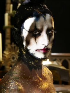 CLOWN EYES AND CONTOURING - contoured cheeks and eyes with gold and black. Fine line detailing and possibly false eyelashes on top and bottom eyelashes.