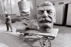 Man dragging bits of Stalin statue after it was legalized to take down the statues of him, Budapest, 1990 [741x495] : HistoryPorn
