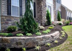 A planter formed from a dry stacked retaining wall was made to match up to the veneer on this house. Front House Landscaping, Landscaping Retaining Walls, Outdoor Landscaping, Outdoor Gardens, Low Retaining Wall Ideas, Landscaping Ideas, Landscaping Blocks, Garden Retaining Wall, Landscape Edging