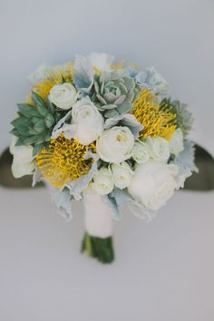 A hand-tied bouquet of yellow pincushion proteas, succulents, white garden roses, and dusty miller foliage | Photo by Fondly Forever Photography | Floral design by Artisan Events