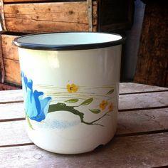 ספל אמייל מקסים מצויר בפרח תכלת/כחול  ופרחים קטנים צהובים.  גובה: 11.5 ס״מ היקף: 12.2 ס״מ