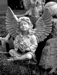 A Petite Angel Clutching Flowers Sits Among Mementos Left at a Grave in St. John's Cemetery on Cambridge Street in Worcester, MA