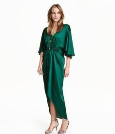 Kleid mit V-Ausschnitt aus glänzendem Webstoff. Modell mit Gummizug in der Taille und kurzen Fledermausärmeln. Abgerundeter Saum und verlängertes Rückenteil. Ungefüttert.
