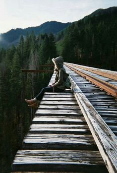 A girl sitting on a train trestle.