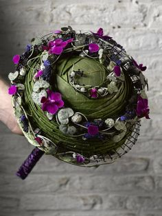 Make a statement with a structured, contemporary take on the round handtied bridal bouquet.  Leaves are intricately folded and then decorated with purple phaleanopsis orchids, blue muscari and ceropegia woodii vine.  This edgier style of bouquet would work well against a classic A-line style bridal gown. By http://valentijnsneek.nl/specialisme/bruidswerk/:
