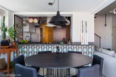 Sala de jantar tem integração com a cozinha através de bancada revestida com ladrilho hidráulico.