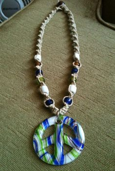 Sold! This hemp necklace is a little over 19 inches. The glass peace sign pendant is white, blue, brown and green. The glass beads used are white, brown, blue and green. The ending bead is a brown wood bead. Each piece of jewlery is handcrafted by me!