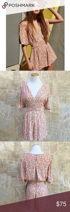 """Free People Romper Free People Meet Virginia Romper. Flirty and fun. Color is pink combo. Split sleeve. V-neck. Zip closure at side, button closure at back. Side pockets. Partially lined. Inseam 2"""", total length 32"""". Size 6 underarm to underarm 15"""", waist 14"""". Size 8 underarm to underarm 16"""", waist 14.5"""". size 10 underarm to underarm 17"""", waist 15"""". Measurements taken flat and are approximate. NWT. A00 Free People Pants Jumpsuits & Rompers"""