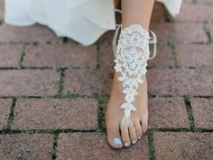 This set of barefoot sandals is created with a simple floral lace. Roundrhinestones and ivory pearls accent the lace and they tie with organzaribbon. One size