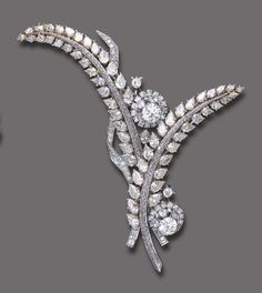 A DIAMOND BROOCH, BY EDMOND FORET   Designed as a stylized spray, composed of two sculpted pear-shaped diamond leaves, with circular-cut diamond stems, enhanced by pear, circular and old European-cut diamond flowers and buds, accented by circular and baguette-cut diamond trim, mounted in white and yellow gold, circa 1955, (may be worn as two brooches)