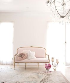Chic French foyer features cream colored walls finished with dentil crown moldings lined with a pink French settee alongside layered Persian rugs.