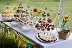 """cupcake table with """"love is sweet"""" bunting"""