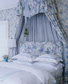 Blue-and-white toile ceiling-mounted crown lined in a coordinating print surrounds the tufted toile-covered headboard.