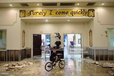 A boy rides his bike inside the flood damaged Life Tabernacle Church on August 15, 2016 in Baton Rouge, Louisiana. Floods ravaged the US state of Louisiana, leaving six people dead and thousands more forced to flee rising waters after days of catastrophic rainstorms. / AFP / Brendan Smialowski