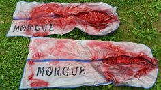 Halloween body bags made from dollar store gown bags, spray insulation foam, and red spray paint.