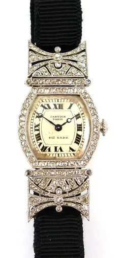 Circa 1920 Art Deco diamond set lady's turtle wristwatch by Cartier, Paris: the tortoise shaped silvered dial with black Roman numerals, rose diamond set bezel and winder, the shaped rectangular shoulders pierced and millegrain set with rose diamonds, mounted in platinum, the case back in gold.