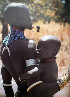 "Africa | Dinka mother and child, Sudan. ""Like the corsets, bracelets and armlets are fitted very tightly to accentuate the body's natural form.  Coils of wire are wound so firmly that they only just permit circulation and often case the limbs to swell, but the Dinka admire roundness of limbs and will endure the discomfort with pride"" 
