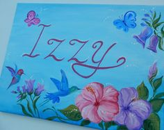 Flowers Girl Name Sign Painting, Custom name sign painting, Personalized girl name canvas painting  Beautiful girl name painting with flowers for your childs room.  Sunrise colors of the background with lively flowers will complement any room color and decor.  Personalized canvas could be a wonderful gift for years to treasure.   This unique girl name painting will add beauty to a room in any color pallet. Great gift of art for a girl any age.  7 x 14 Original painting with acrylic on canvas…