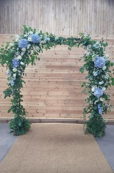 Flowers by Jennifer Pinder. A pale blue and white flower arch arbour at a countryside wedding in a traditional barn in Chafford Park, Kent. The arch uses hydrangea, baby's breath, scabious, dahlias, delphinium and stock.