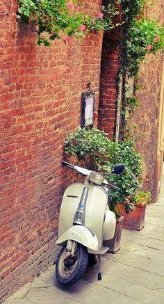 vespa parked on brick wall