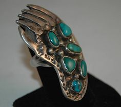 This is a big 2 1/2 tall and heavy thick sterling vintage Navajo Tyron and Morenci Turquoise ring! The stones are a gorgeous deep blue with some having a black matrix and silver pyrite! All stones are set deep in a hand wrought large thick sterling stamped and incised beautiful Bear Claw! Large sterling raindrops are almost hidden under the heavy patina and the edges have sweet stamp work that trails up to the Bear Claws! Stunning details! The substantial ring is placed on a well made 3 ...