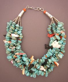 Necklace    Anne Holland ~ Dorje Designs.    Native American fetishes carved from spondylus (spiny oyster) shell are placed throughout five strands of turquoise beads.
