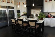"""""""Gourmet Saturday"""" Kitchen of the Day: A black-and-white kitchen with marble island countertops, an island sink, a pot filler, island seating for guests, a professional range under a massive wood hood, and TWO glass door refrigerators!"""